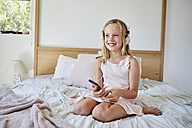 Portrait of smiling little girl sitting on bed listening music with headphones - SRYF00262