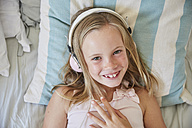 Portrait of smiling little girl lying on bed at home listening music with headphones - SRYF00265