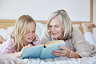 Little girl lying on the bed with her grandmother reading a book - SRYF00271