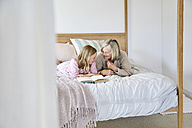 Little girl lying on the bed with her grandmother talking together - SRYF00274
