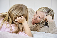 Senior woman relaxing with her granddaughter on the bed - SRYF00280