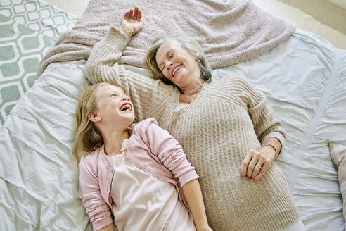 Little girl lying on the bed with her grandmother having fun - SRYF00283