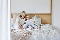 Laughing little girl lying on the bed with her grandmother using tablet - SRYF00286
