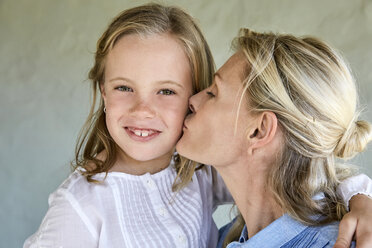 Portrait of smiling little girl kissed by her mother - SRYF00322