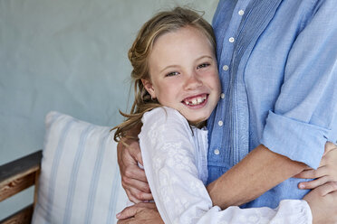 Portrait of smiling little girl with tooth gap hugging her mother - SRYF00325