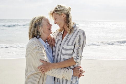 Senior woman and her adult daughter standing on the beach, embracing - SRYF00346