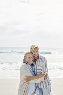 Senior woman and her adult daughter standing on the beach, embracing - SRYF00349