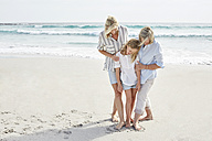 Mother, daughter and grandmother standing in a heart, drawn into the sand on the beach - SRYF00352