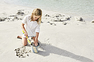 Little girl playing on the beach with bucket and shovel - SRYF00358