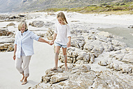 Grandmother and granddaughter walking on the beach, holding hands - SRYF00361