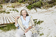 Senior woman sitting on the beach, looking at camera - SRYF00367