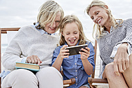 Mother, daughter and grandmother taking smartphone selfies on the beach - SRYF00376
