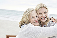 Mother and daughter embracing on the beach - SRYF00385
