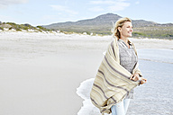 Mature woman enjoying the sea, wrapped in a blanket - SRYF00394