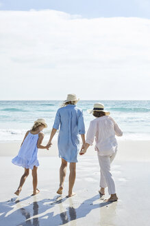 Mother, daughter and grandmother walking by the sea, rear view - SRYF00406