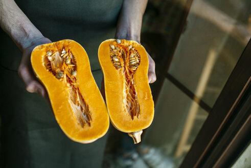 Man's hands holding a sliced pumpkin, close-up - KIJF01418