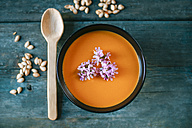 Bowl of creamed pumpkin soup with edible flowers - KIJF01427