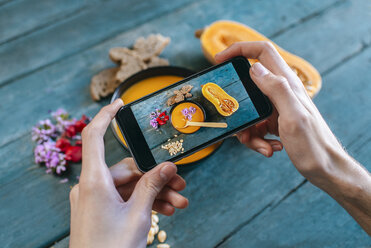 Close-up of man's hands taking picture of creamed pumpkin soup with smartphone - KIJF01433