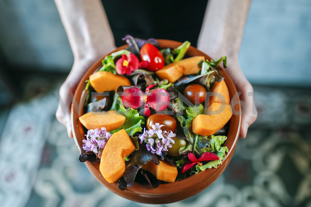 Man's hands holding bowl of mixed salad garnished with edible flowers, close-up - KIJF01439