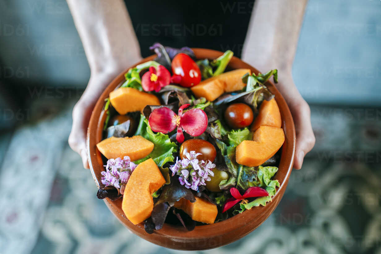 Man's hands holding bowl of mixed salad garnished with edible flowers, close-up - KIJF01439 - Kiko Jimenez/Westend61