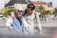 Happy senior man with adult grandson in the city on the move - UUF10416