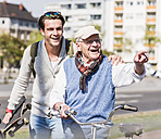 Happy senior man with adult grandson in the city on the move - UUF10419