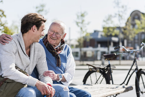 Happy senior man with adult grandson sitting on a bench - UUF10422