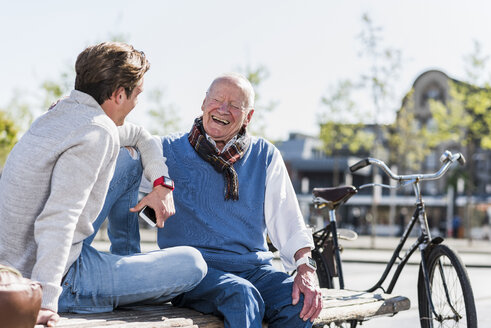 Laughing senior man with adult grandson on a bench - UUF10425