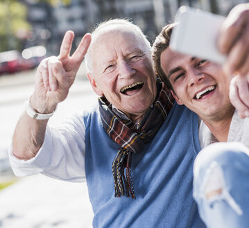 Happy senior man and adult grandson taking a selfie - UUF10431