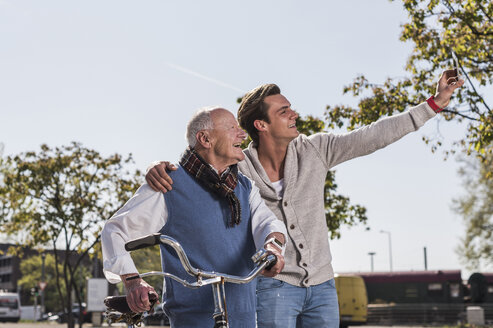 Senior man and adult grandson taking a selfie outdoors - UUF10437