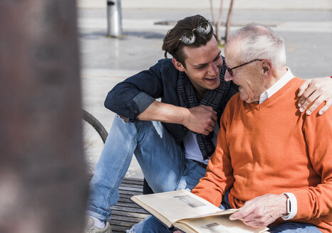 Happy senior man and adult grandson with photo album outdoors - UUF10452