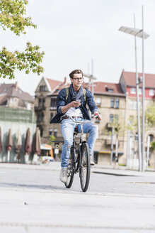 Young man with bicycle in the city holding cell phone - UUF10464