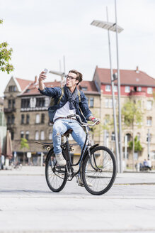 Playful young man with bicycle in the city using cell phone - UUF10467