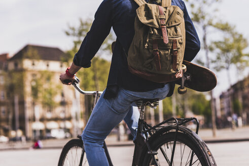 Young man holding skateboard riding bicycle in the city - UUF10470