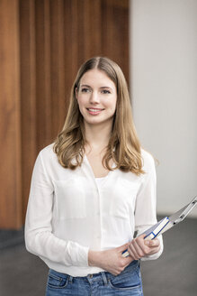 Portrait of smiling young businesswoman with notebook and clip board - PESF00533