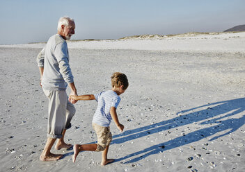 Grandfather and grandson strolling on the beach - RORF00755
