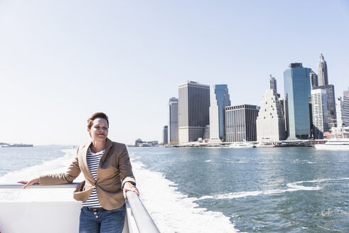 USA, New York City, woman on ferry with Manhattan skyline in background - UUF10477