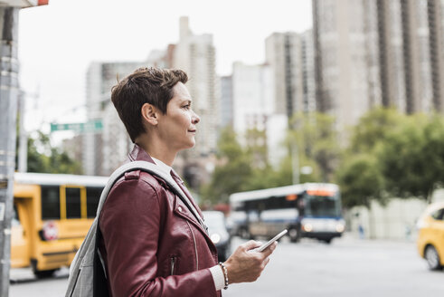 USA, New York City, woman with cell phone in the city - UUF10483