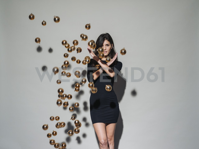 Portrait of young woman surrounded by Christmas baubles floating mid-air - KNSF01228