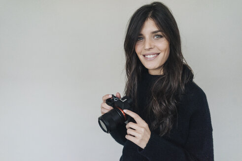 Smiling dark-haired young woman holding a camera - KNSF01237