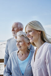 Smiling senior couple with adult daughter on the beach - RORF00762
