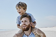 Father carrying son piggyback on the beach - RORF00765
