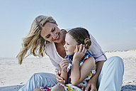 Happy mother and daughter holding seashell on the beach - RORF00771