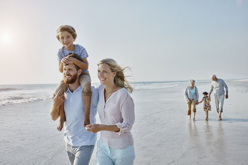Happy extended family strolling on the beach - RORF00789
