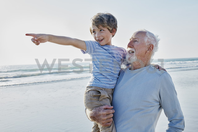 Grandfather carrying grandson on the beach - RORF00795