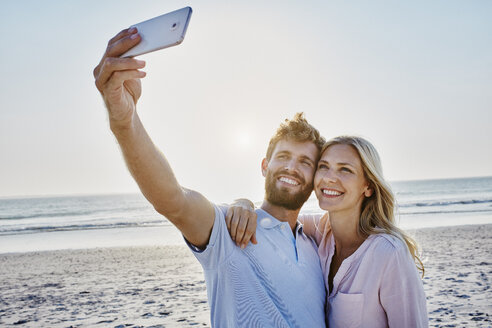 Happy couple taking a selfie on the beach - RORF00807