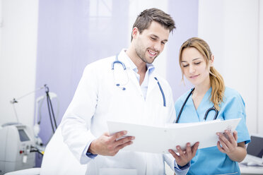 Two smiling doctors holding folder - WESTF22982