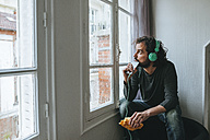 Man listening music with headphones and smartphone at home - KIJF01441