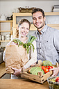 Smiling couple with box of vegetables in kitchen - WESTF23006