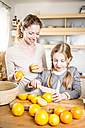 Mother and daughter cutting oranges in kitchen - WESTF23009
